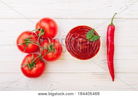 Tomato ketchup sauce in a bowl with chili basilic and tomatoes. Ingredients for cooking ketchup. Top view