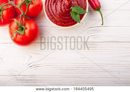 Tomato ketchup sauce in a bowl with chili basilic and tomatoes. Ingredients for cooking ketchup on white wooden background. Top view . Copy space