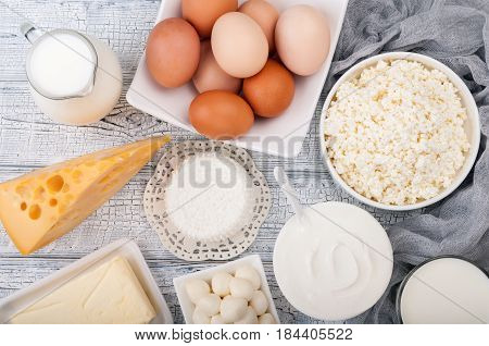 Dairy products on wooden table. Milk sour cream cheese egg yogurt and butter. Healthy food diet concept. Copy space. Top view
