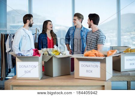 Smiling creative business team talking near the donation box in office