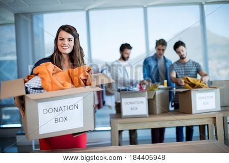 Portrait of smiling woman holding a donation box in office