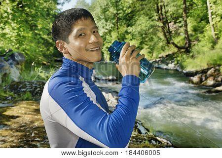 Mixed race man drinking water near river