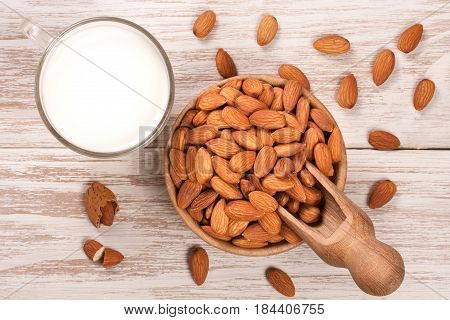 Almond milk in a glass and almonds in a bowl on light wooden background. Top view.