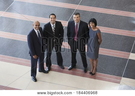 Smiling business people standing in lobby