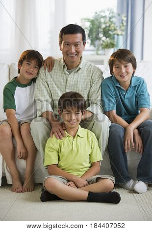 Smiling father and sons in living room