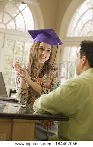 Father admiring daughter's graduation cap