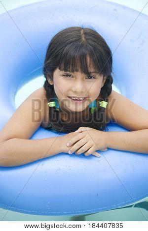 Smiling Hispanic girl with inner tube in swimming pool