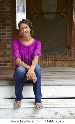 Mixed race woman sitting on front stoop