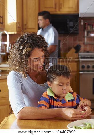 Mother and son shelling peas at dining table