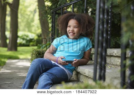 Smiling mixed race girl holding cell phone on front stoop
