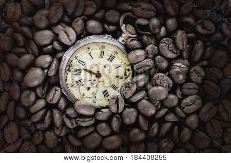 Coffee time. vintage decayed pocket watch with roasted coffee beans