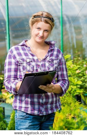 Woman With A Folder Of Readings Recorded Growth Of Plants In The Greenhouse