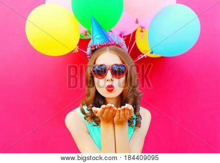 Portrait Pretty Woman In A Birthday Cap Is Sends An Air Kiss Holds An Air Colorful Balloons On A Pin