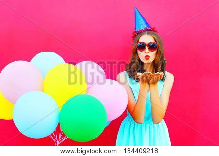 Pretty Woman In A Birthday Cap Is Sends An Air Kiss Holds An Air Colorful Balloons On A Pink Backgro