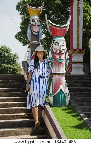 Asian Thai Woman Travelers Visit And Portrait With Phi Ta Khon Statue For Writing Blog At Phi Ta Kho