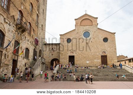 SAN GIMIGNANO ITALY - August 1 2015: Tourists in the village of San Gimignano Italy a medieval walled city in the province of Siena in Tuscany. The city is a popular tourist destination, famous for it's well-preserved churches walls, and stone towers.