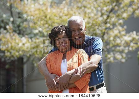 Smiling Black couple hugging outdoors