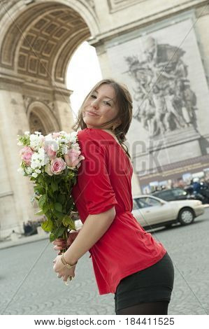 Caucasian woman holding bouquet near Arc de Triomphe