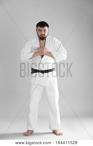 Young sporty man in kimono on light background