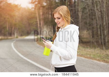 Outdoor Messaging. Portrait Of Young And Beautiful Redhaired Sports Girl Using Her Phone And Keeping