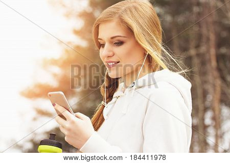 Sports Beauty. Closeup Portrait Of Smiling Young And Beautiful Redhaired Sports Girl Using Her Phone