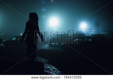 Lonely man in darkness. City at night in dense fog in darkness. Thick smog on a street darkness. Beautiful mixed lighting from windows. Silhouettes of people and trees in darkness. Pillars at road in darkness