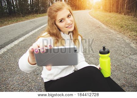 Selfie Time. Portrait Of Pretty And Young Redhaired Sports Girl Taking A Selfie While Sitting On The