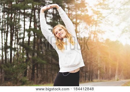 Healthy Lifestyle. Portrait Of Young And Cheerful Redhaired Sports Girl Doing Stretching In The Park
