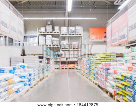 Abstract blurred hardware store aisle with colorful shelves and unrecognizable customers as background