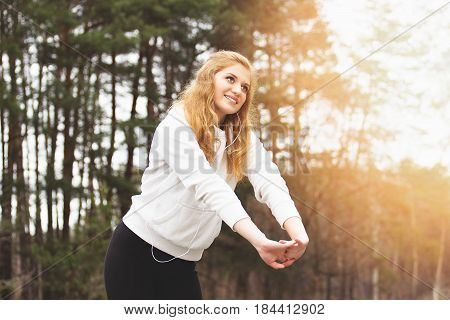 Morning Fitness. Portrait Of Cheerful And Young Redhaired Sports Girl Doing Stretching In The Park.