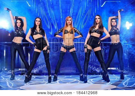 Gorgeous young sexy go-go dancers wearing identical black outfits dancing on stage at the night club erotic exotic seductive sexy hot performance show diverse ballet disco clubbing nightlife.