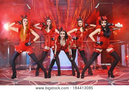 Five beautiful young athletic girls wearing red sexy outfits dancing at the nightclub entertainment luxury erotic exotic dancers group showgirls carnival masquerade seductive feminine lifestyle.