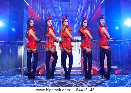 Group of five beautiful sexy go-go dancers looking to the camera seductively over their shoulders posing at the nightclub performance disco outfits group showgirls ballet dance dancing entertain.