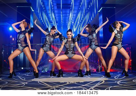 Group of sexy stunning young girls dancing together at the nightclub on stage entertainment leisure disco celebration festive show showgirls ballet diverse outfits stage costumes go-go concept.