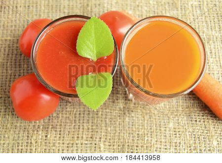 Tomato juice and juice carrot are poured in glasses. Tomatoes and carrots are located a row.