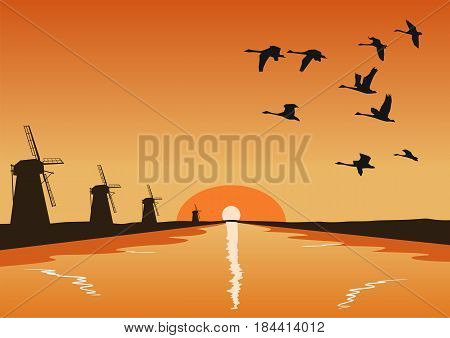 Flock of geese flying over river with mills at the sunset