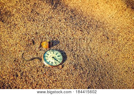 Still life - Antique rotten pocket watch and sea shell buried partial in the sand.