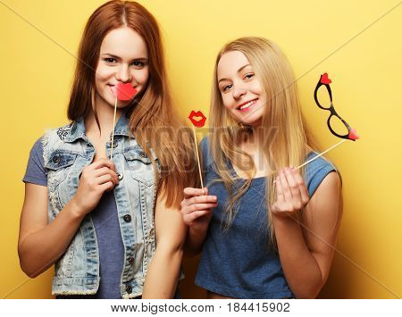 two stylish sexy hipster girls best friends ready for party, over yellow  background