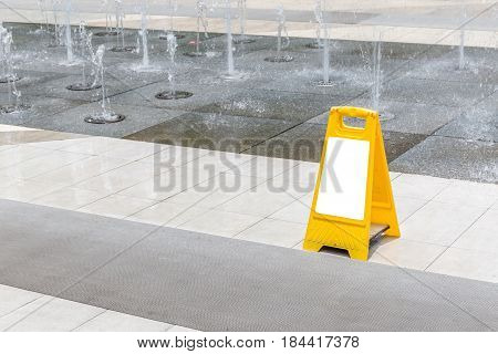 Blank yellow hazard sign alerts for a wet floor in fountain decoration area.