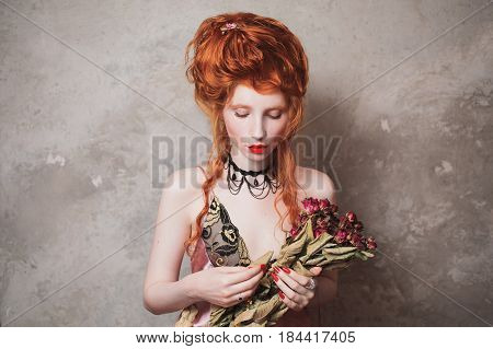 Attractive woman with red hair in a nightgown. Red-haired attractive girl with pale skin and blue eyes with bright unusual appearance with choker around her neck on a background of gray wall. French attractive courtesan. Copyspace. Attractive model