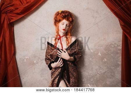 Art woman with red hair in leopard print art gown with a gun in his hand. Red-haired art girl with pale skin and blue eyes with a bright unusual appearance with a red ribbon around her neck. French courtesan. Retro art. Vintage art. Art concept. Art idea