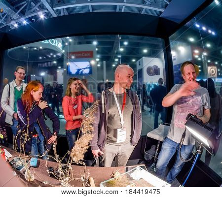 MOSCOW RUSSIA - APRIL 21 2017: Attendees of macro photography workshop at booth of Olympus company at PhotoForum 2017 put millipede for fun on bald spot in Moscow Russia on April 21 2017.