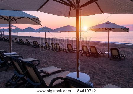Row of sunshade umbrellas on sea beach. Tranquil view of the Mediterranean sea. Amazing pink sunrise with clear sky. Location place: Turkey, Kemer.
