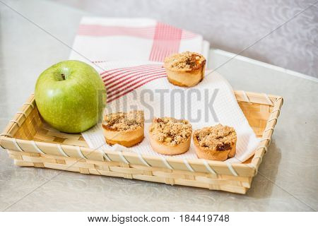 Magnificent portioned tartlet cakes with sweet stuffing. Professional baking. Background of wicker basket, white dish towel and green apple