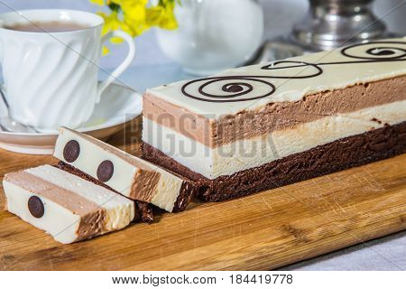 Three-layer chocolate cake, decorated with chocolate patterns. Professional bakery. Background - porcelain cup with hot tea. Holiday cake Three-colate