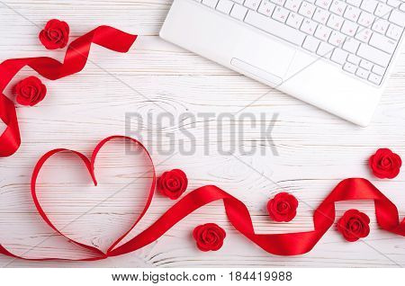 Valentines background with red heart laptop and roses. Valentines Day greeting card. Female workplace. Top view