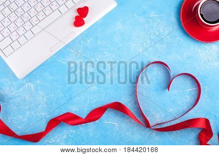 Valentines background with red heart coffee cup and laptop. Valentines Day greeting card. Female workplace. Top view