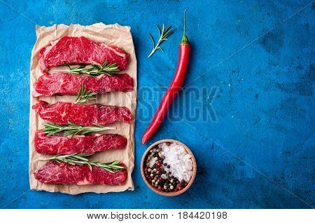 Raw meat on stone background. Raw beff stroganoff with herbs and spices. Cooking meat. Copy space. Top view