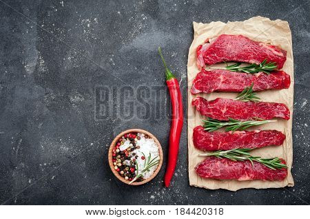 Raw meat on dark background. Raw beef stroganoff with herbs and spices close up. Cooking meat. Copy space. Top view