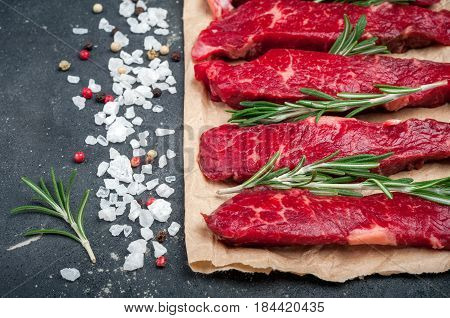 Raw meat on dark background. Raw beef stroganoff with herbs and spices close up. Cooking meat. Top view